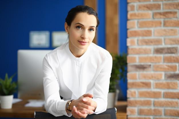 Bizneswoman pozycja w biurze opiera na krześle
