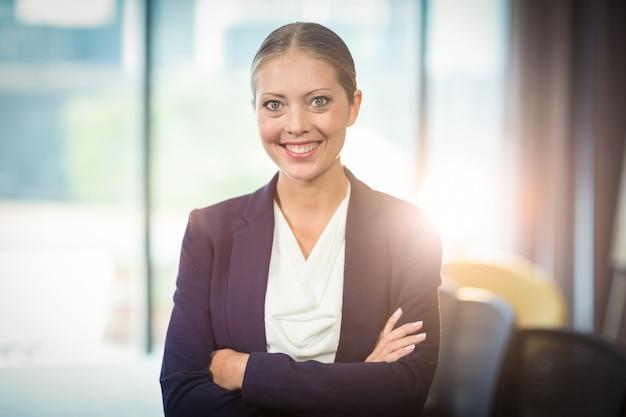 Bizneswoman pozycja z rękami krzyżował w biurze