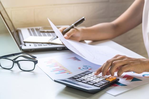 Bizneswoman pracuje na biurka biurze z marketingową wykres statystyk analizą