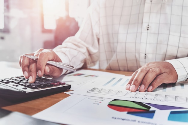 Bizneswoman pracuje na biurku w biurze i używa kalkulatora i laptopu