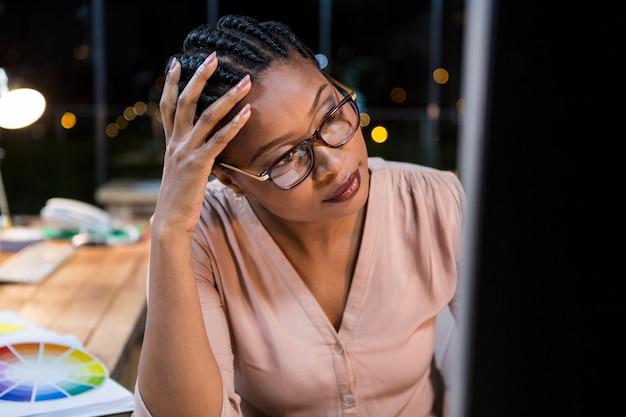 Bizneswoman pracuje na komputerze przy jej biurkiem