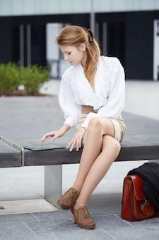 Bizneswoman pracuje na zewnątrz budynku biurowego z cyfrowymi urządzeniami