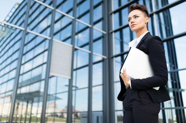 Bizneswoman pracuje outdoors z laptopem