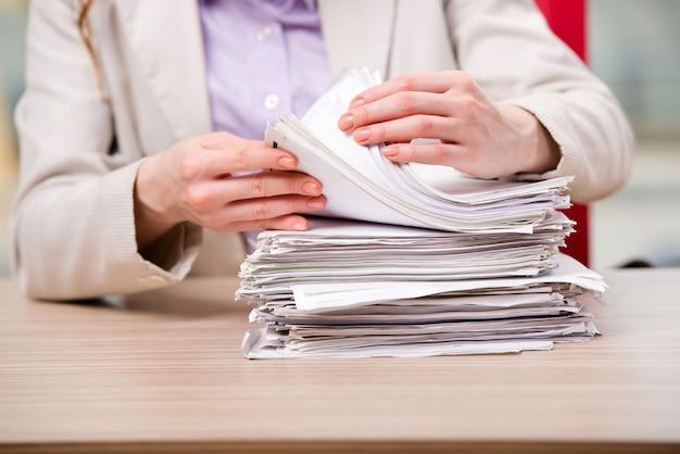 Bizneswoman pracuje z stertą papiery