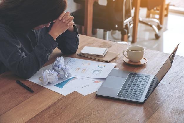 Bizneswoman pracuje z uczuciem sfrustrowania i zestresowania z posprzątanymi papierami i laptopem na stole w biurze