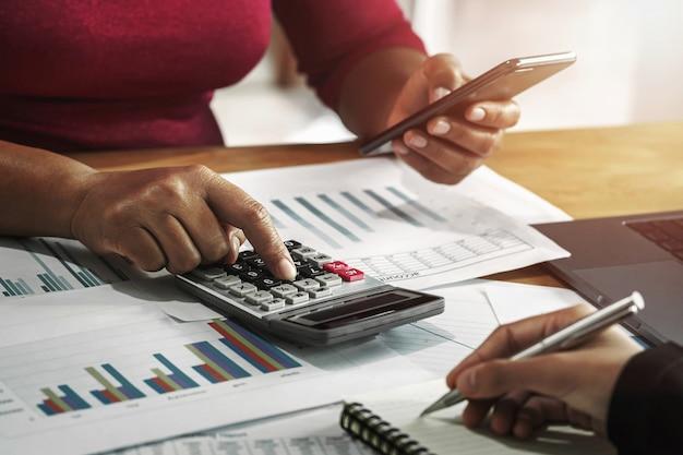Bizneswoman pracuje z używać kalkulatora i wiszącej ozdoby w biurze