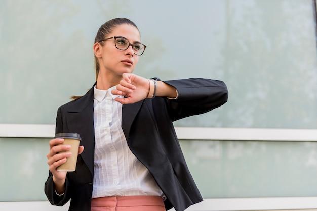 Bizneswoman przed budynkiem patrzeje na zegarku i pije kawę