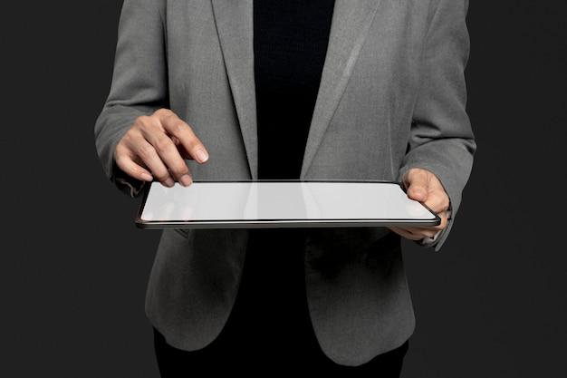 Bizneswoman przedstawiający niewidzialny hologram wystający z zaawansowanej technologii tabletu