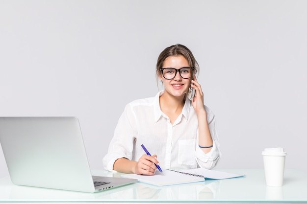 Bizneswoman przy jej pracującym biurkiem z laptopem i opowiadać telefonem odizolowywającymi na białym tle