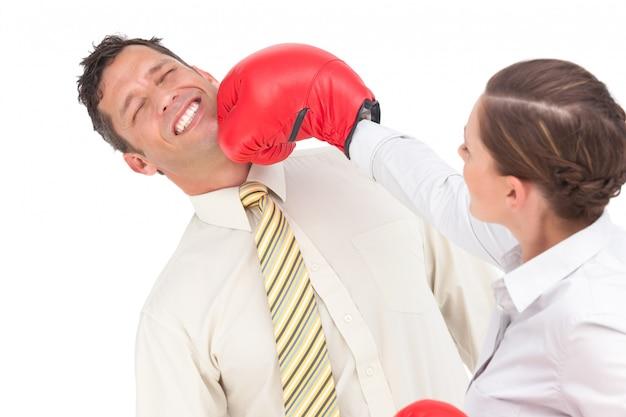 Bizneswoman puka out biznesmena z bokserskimi rękawiczkami