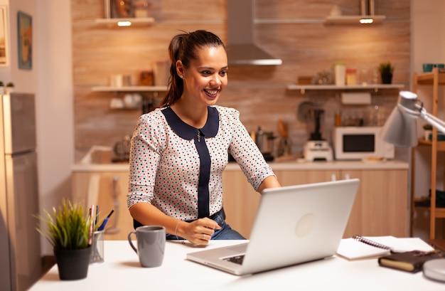 Bizneswoman reagując z podekscytowaniem podczas pracy nad ważnym projektem wieczorem. pracownik korzystający z nowoczesnych technologii o północy wykonujący nadgodziny w pracy, biznesie, karierze, sieci, stylu życia.