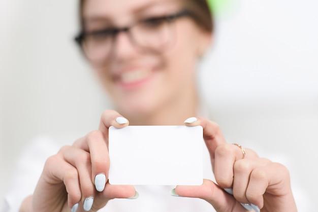 Bizneswoman ręka pokazuje pustą białą wizytówkę w kierunku kamery