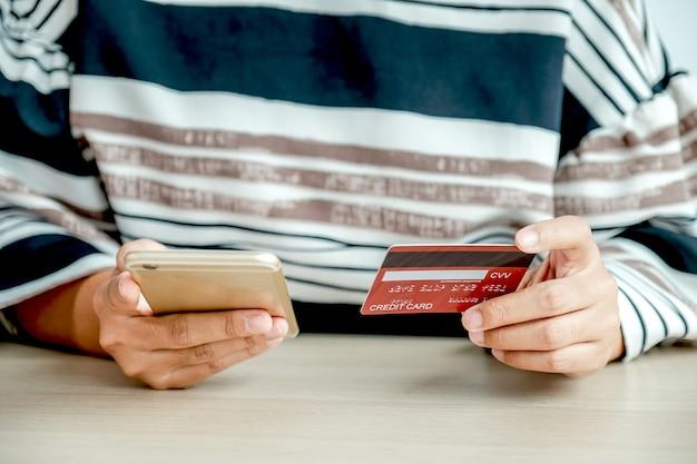 Bizneswoman ręka trzyma kartę kredytową do zakupów online z domu, wydawania pieniędzy za pomocą smartfona