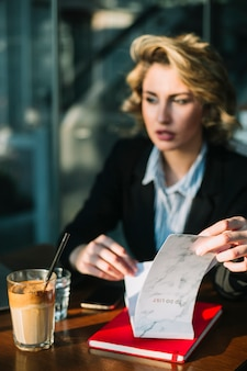 Bizneswoman ręka trzyma robić liście z czekoladowym milkshake na drewnianym biurku