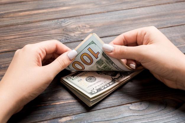 Bizneswoman ręki liczy pięć i sto dolarowych banknotów na drewnianym tle