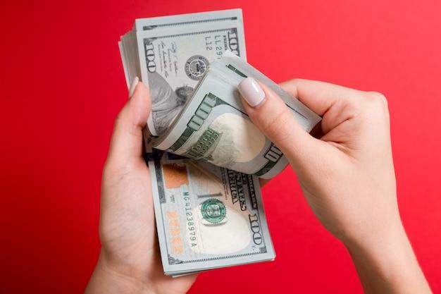Bizneswoman ręki liczy sto dolarowych rachunków na kolorowej ścianie. pojęcie wynagrodzenia i płacy. widok z góry koncepcji inwestycyjnej