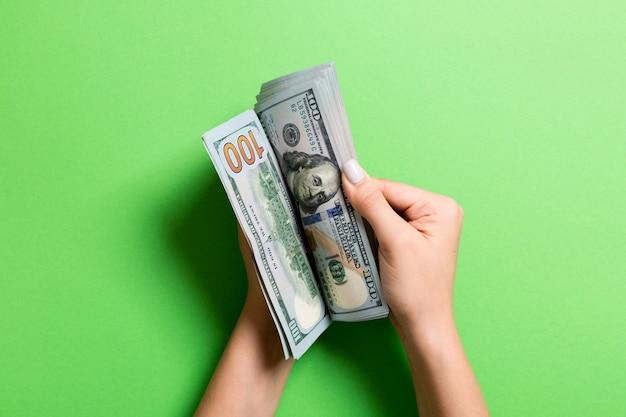 Bizneswoman ręki liczy sto dolarowych rachunków na kolorowym. pojęcie wynagrodzenia i płacy. widok z góry koncepcji inwestycyjnej