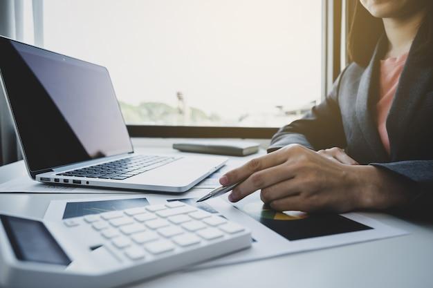 Bizneswoman ręki trzymającej pióro, analizuje wykres z kalkulatorem i laptopem w domowym biurze do wyznaczania ambitnych celów biznesowych