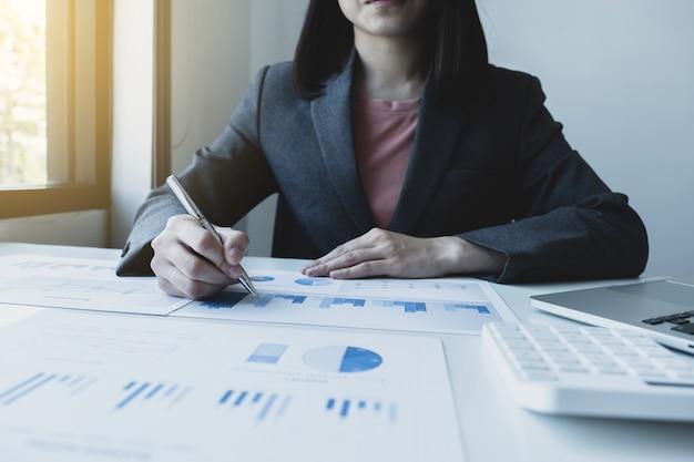 Bizneswoman ręki trzymającej pióro analizy wykresu z kalkulatorem i laptopem w biurze domowym