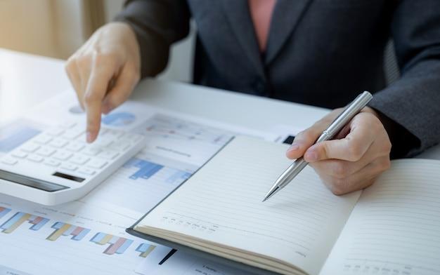 Bizneswoman ręki trzymającej pióro i analizy wykresu z laptopem w domowym biurze