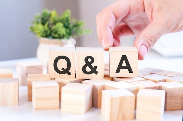 Bizneswoman ręki trzymającej q i a słowo z drewnianym blokiem kostki. odpowiedź, pytanie, informacje, koncepcje komunikacji