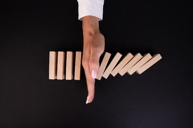 Bizneswoman ręki zatrzymanie spadających bloków drewnianych lub domino zarządzanie ryzykiem biznesowym