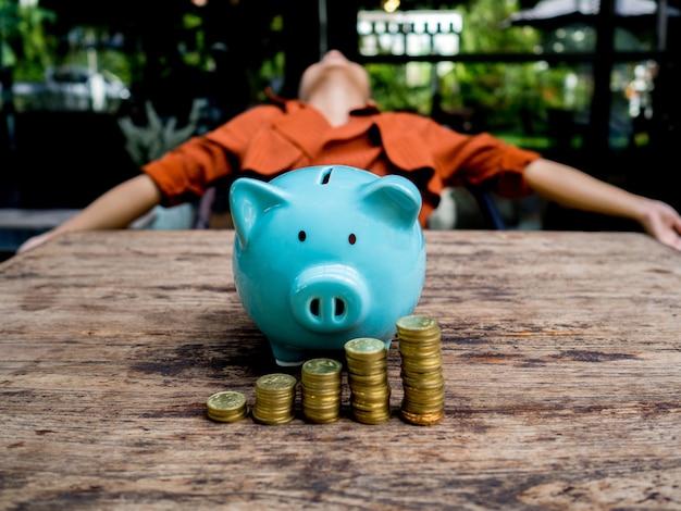 Bizneswoman relaksuje się za niebieską skarbonką ze stosem złotych monet oszczędzanie pieniędzy na fundusz emerytalny