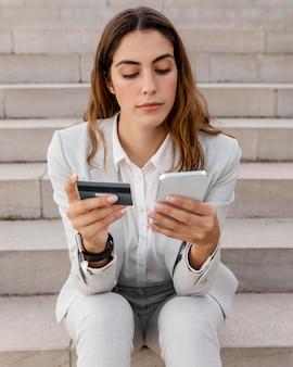 Bizneswoman robi zakupy online za pomocą smartfona i karty kredytowej