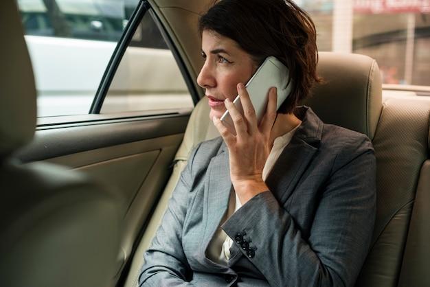 Bizneswoman rozmawia za pomocą telefonu wewnątrz samochodu