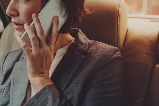 Bizneswoman rozmawiający za pomocą telefonu wewnątrz samochodu