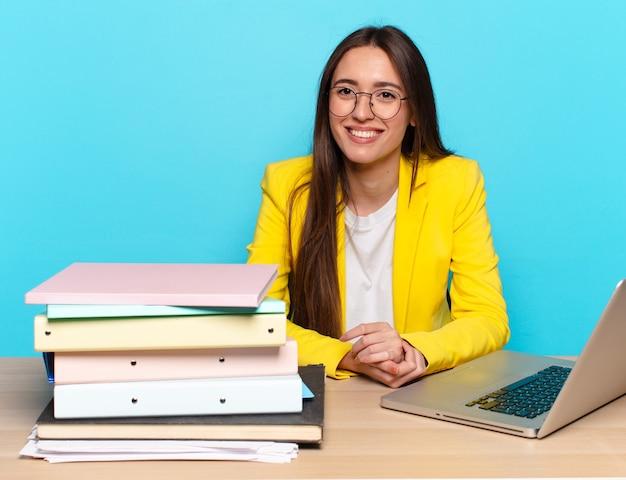 Bizneswoman siedząca na biurku pracująca z laptopem