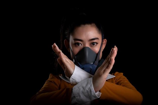 Bizneswoman stawia na maskę n95 respiratora i pokazuje znak stop