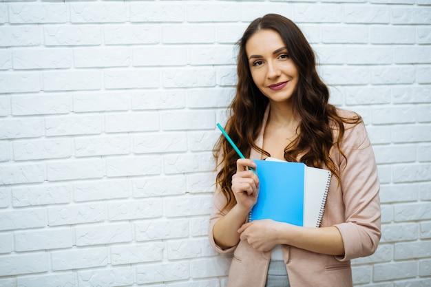 Bizneswoman stoi blisko białego ściana z cegieł