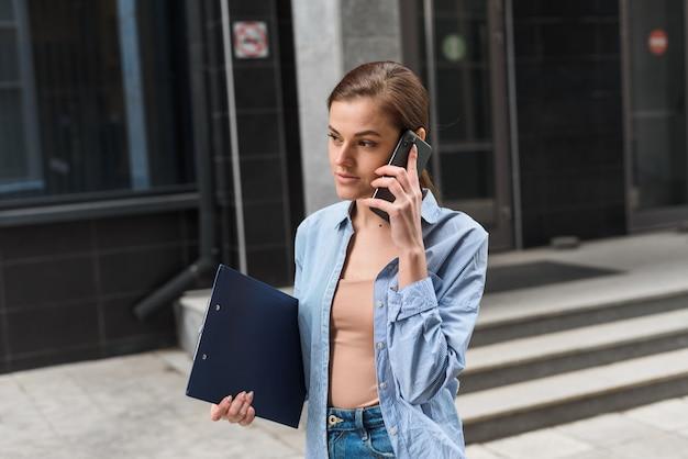 Bizneswoman stoi na tle centrum biurowego, uśmiecha się i rozmawia przez telefon. komunikacja z partnerami biznesowymi na odległość. młoda kobieta w stylu biznesowym