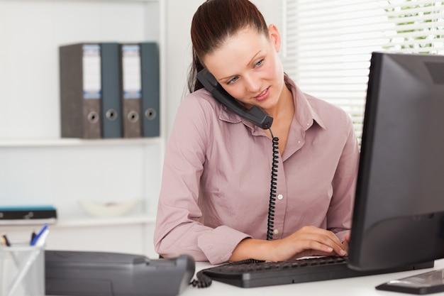 Bizneswoman telefonuje i pisać na maszynie