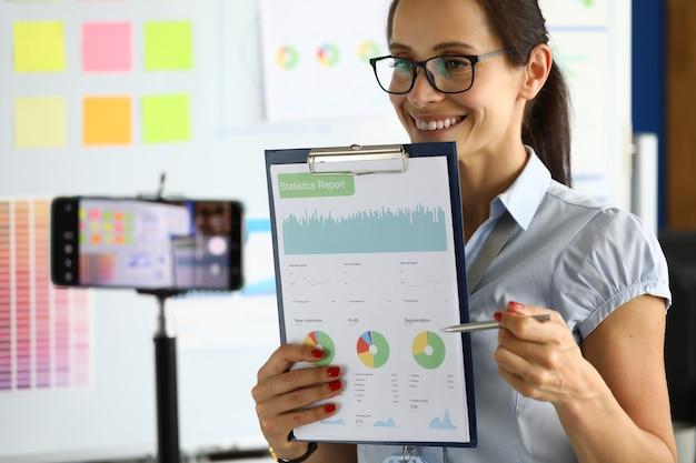 Bizneswoman transmituje wideokonferencję na smartfona, pokazując komercyjne wyniki.