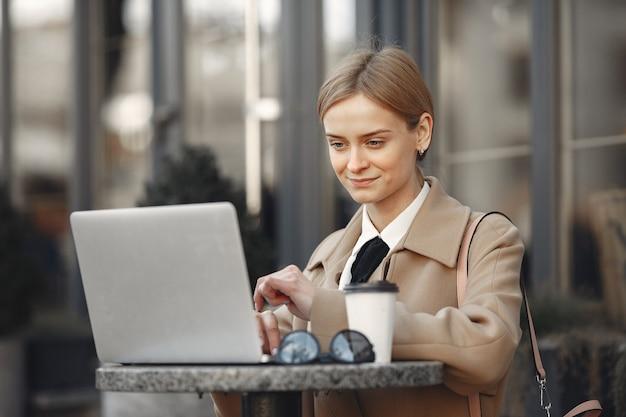 Bizneswoman trwanie outside z laptopem i kawą