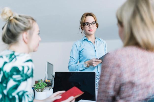 Bizneswoman trzyma cyfrową pastylkę opowiada z jej kolegami