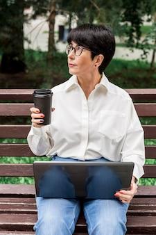 Bizneswoman trzyma filiżankę kawy i odwracając