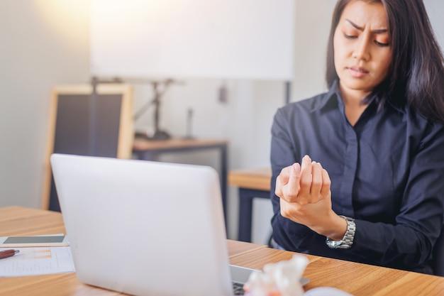 Bizneswoman trzyma jej nadgarstek objawowy z bolesnym. koncepcja zespołu biurowego