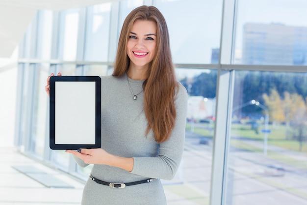 Bizneswoman trzyma pastylkę w jego rękach przy biurem