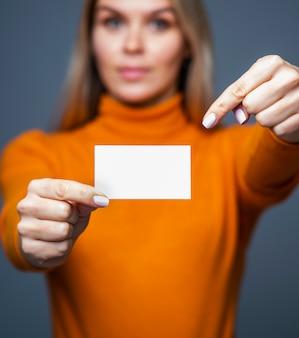 Bizneswoman trzyma pustą wizytówkę