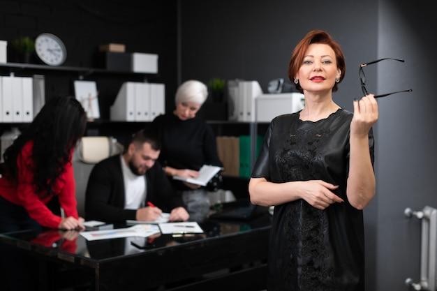 Bizneswoman trzyma szkła na pracownikach biurowych dyskutuje projekt