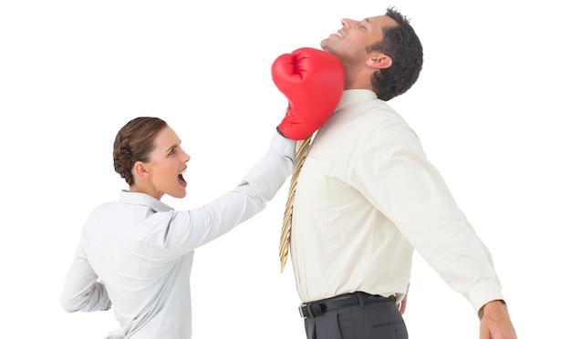 Bizneswoman uderza biznesmena z bokserskimi rękawiczkami