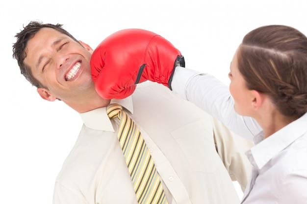 Bizneswoman uderza pięścią biznesmena z bokserskimi rękawiczkami
