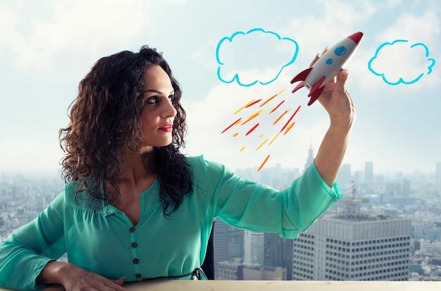 Bizneswoman uruchamia swoją firmę z zabawkową rakietą. pojęcie startupu i innowacji