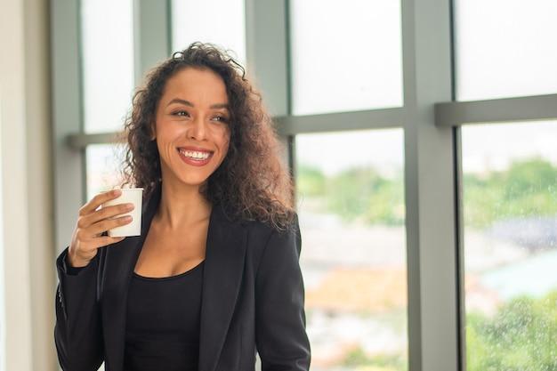 Bizneswoman uśmiech szczęśliwy w czasie kawy w biurze