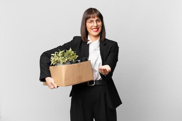 Bizneswoman uśmiecha się radośnie z przyjaznym, pewnym siebie, pozytywnym spojrzeniem, oferując i pokazując przedmiot lub koncepcję