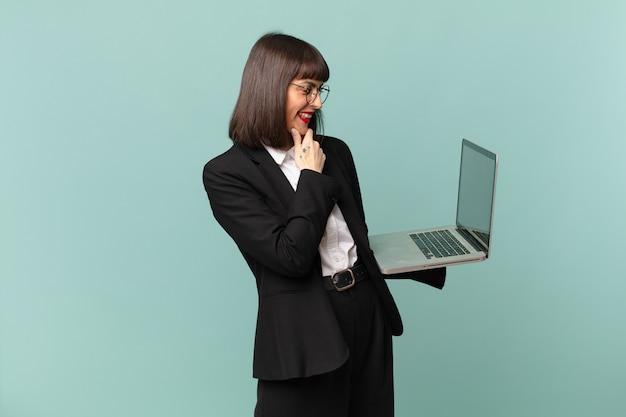 Bizneswoman uśmiecha się ze szczęśliwym, pewnym siebie wyrazem twarzy z ręką na brodzie, zastanawiając się i patrząc w bok