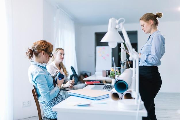 Bizneswoman używa cyfrową pastylkę stoi blisko jej kolegi obsiadania w biurze